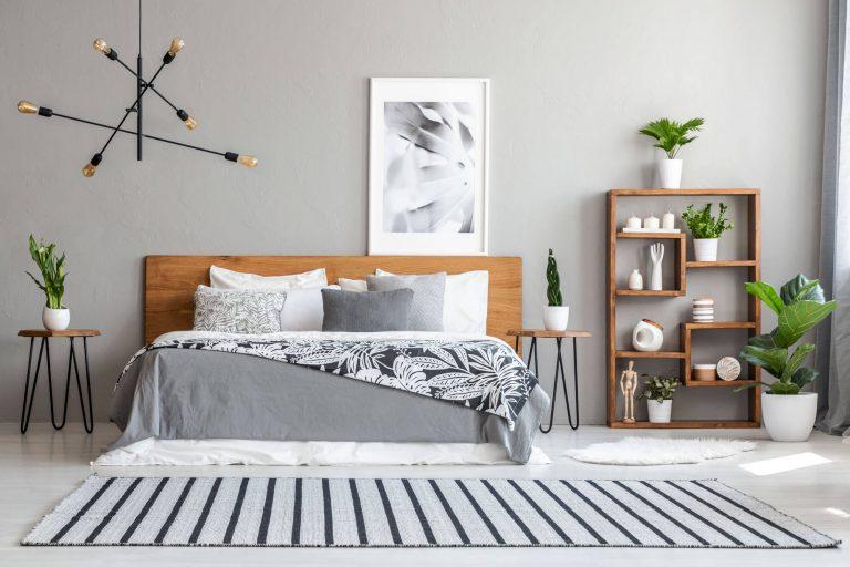 gestreifter Teppich liegt vor einem Bett mit unifarbenen und gemusterten Heimtextilien