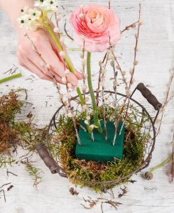 Drahtkorb mit Moos, Gesteckhalter, Blumen und einzelnen Zweigen