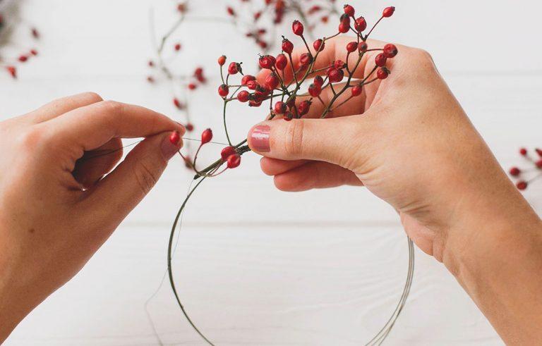 Frauenhände stecken Beerenzweige an ein rundes Draht und bauen einen Beerenkranz in Rot