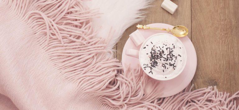 Rosa Decke, rosa Tasse und goldener Löffel
