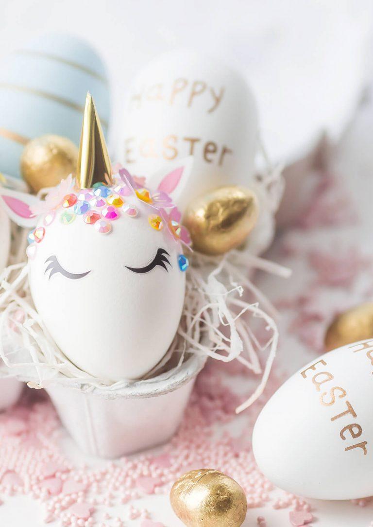 Dekorierte Eier in Eierkarton verziert als Einhorn und Osterbeschriftung