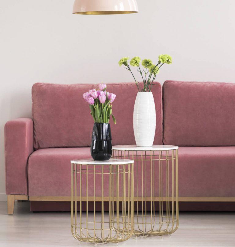 Rosa Couch mit goldenen Tischchen und Blumen drauf