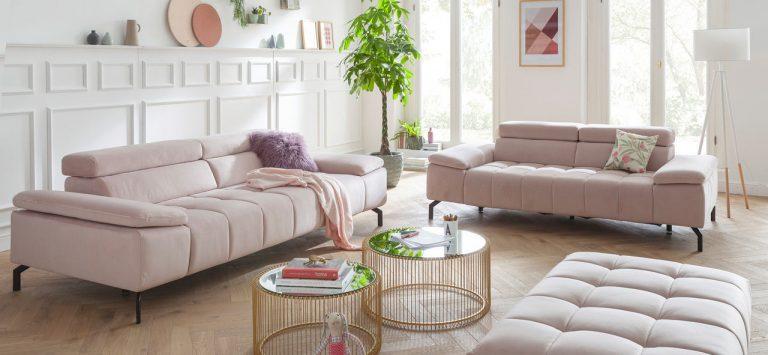 Rosa Sofa mit goldenen Tischchen in weißem Wohnzimmer