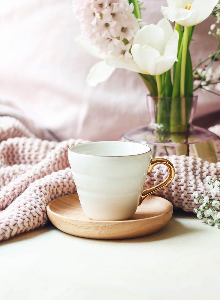 Kleine weiße Tasse mit goldenem Griff, rosa Häckeldecke und Blumen