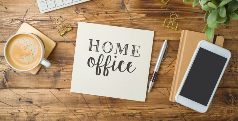 Schreibtisch von oben mit Kaffee, Smartphone, Notizbuch etc.