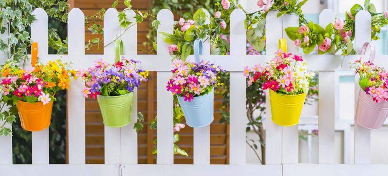 Blumentöpfe mit Blumen an weißem Gartenzaun