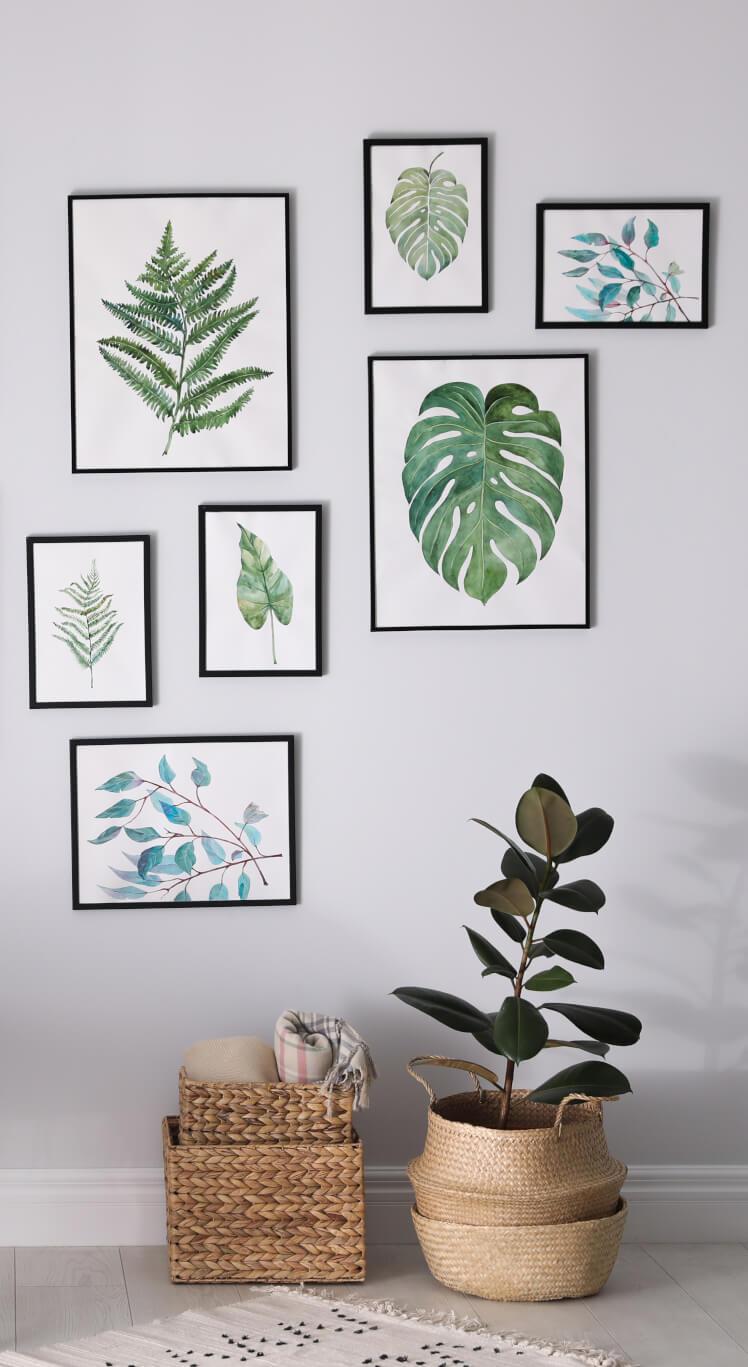 Wand mit vielen Bilderrahmen und Deko-Körben darunter