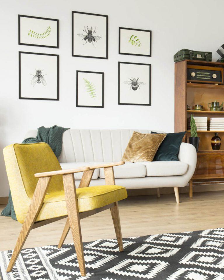 Gelber Sessel und helles Sofa, dahinter Bilderrahmen an der Wand