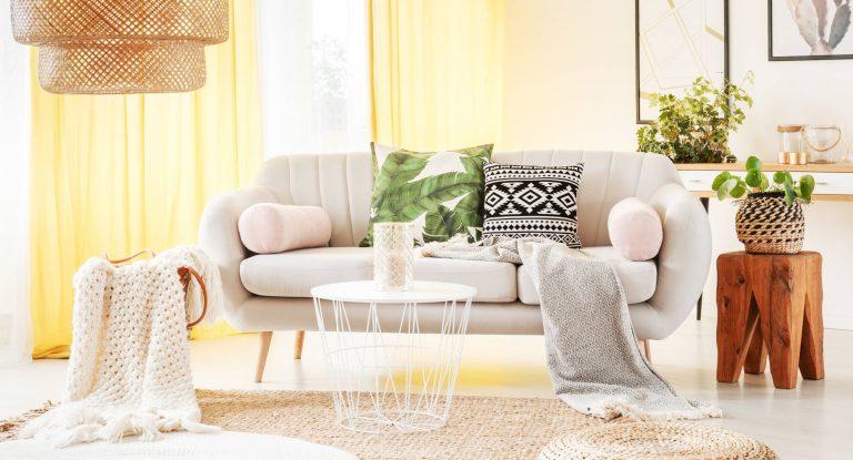 Helles Sofa mit Deko-Kissen vor gelber Wand