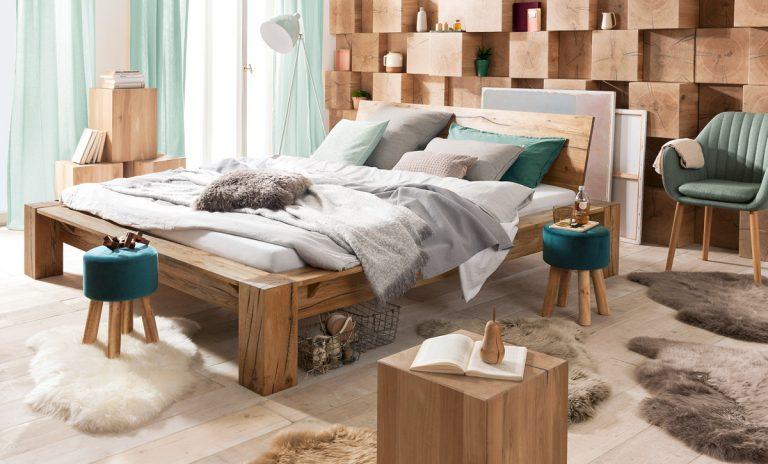 Bett aus dicken Holzbalken mit kleinen Hockern davor