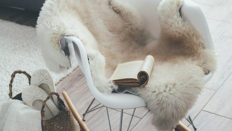 Stuhl mit Schaffell und Buch