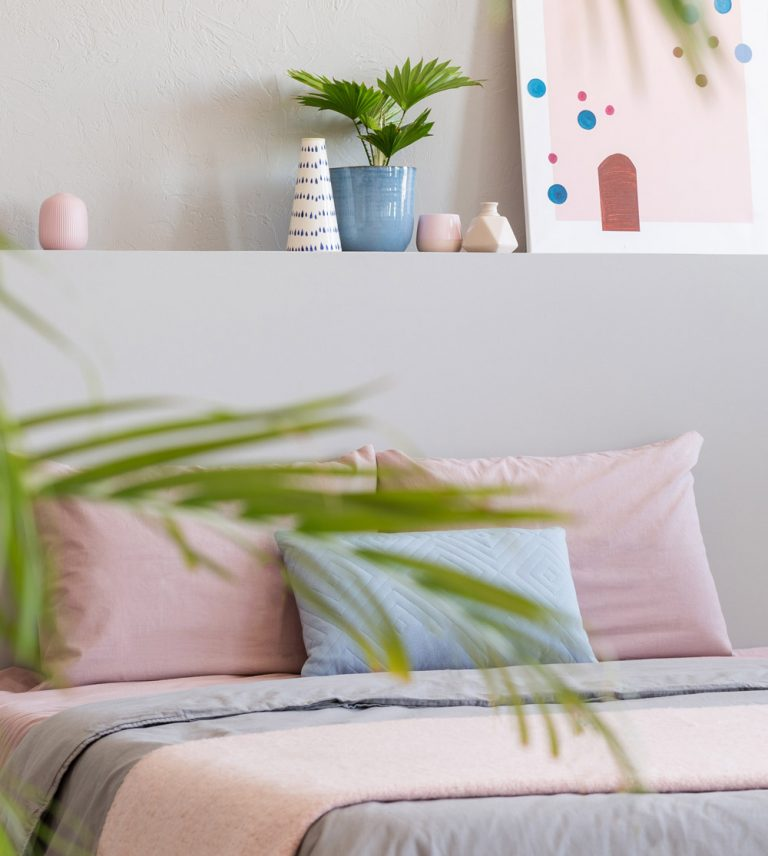 Bett mit Kissen und Decke in Pastell