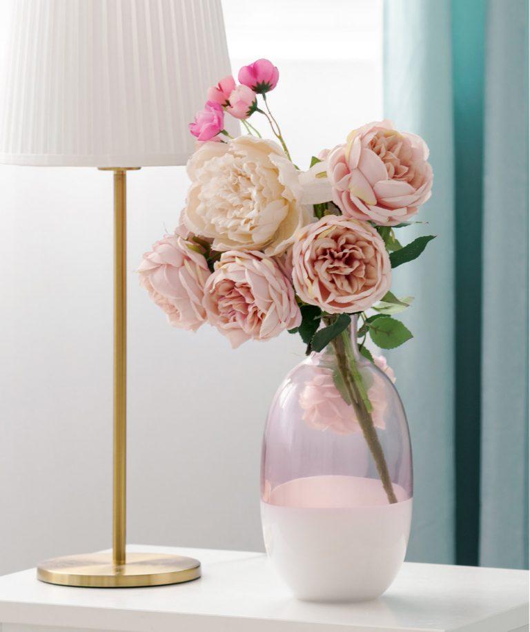 Blumen in Glasvase und goldene Tischleuchte mit hellem Lampenschirm