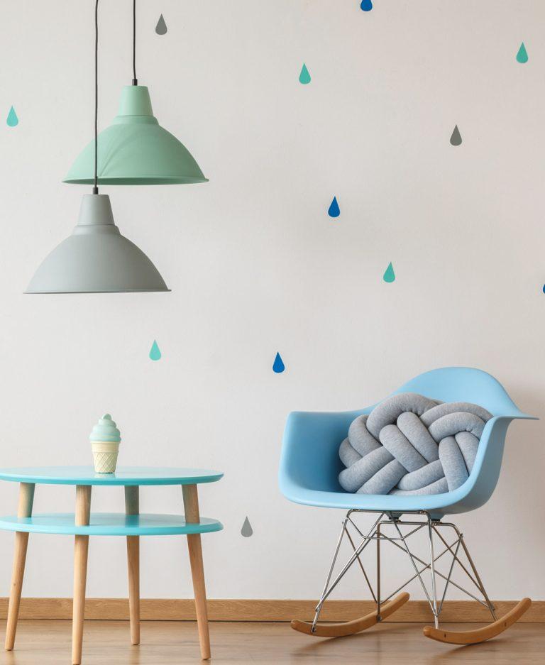 Kinderzimmer mit Schuakelstuhl, Tisch und Deckenlampe in Pastellfarben