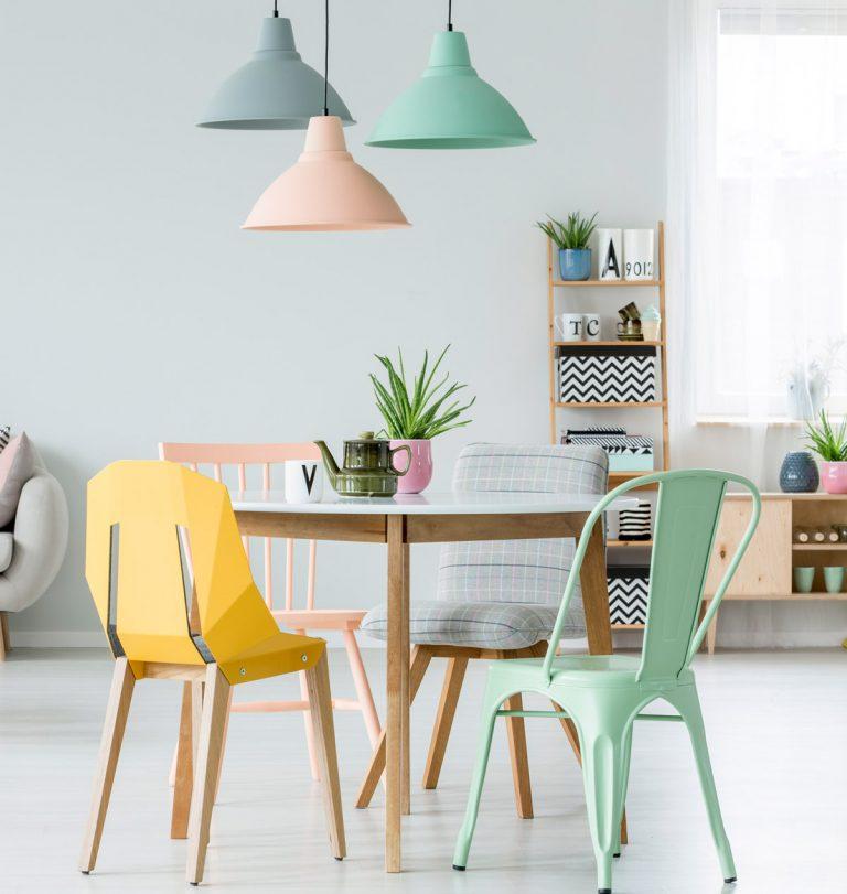 bunte Stühle mit kleinem Tisch und pastellfarbenen Deckenlampen