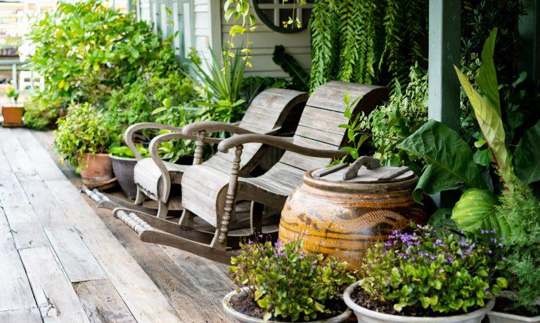 Schaukelstühle auf Veranda mit Pflanzen