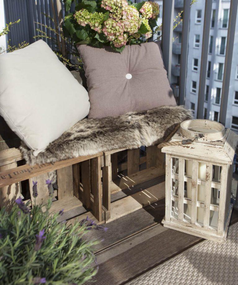 Balkon mit Bank aus Weinkisten, Fell, Kissen und Lampe