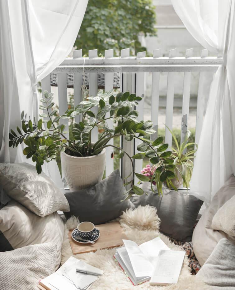 Balkon mit vielen Kissen, Vorhang und Pflanze