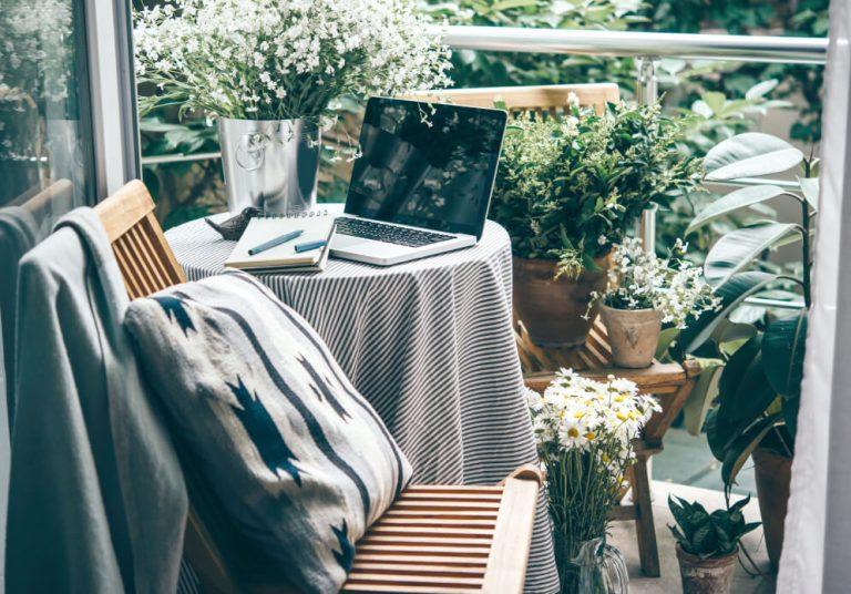 Arbeitsplatz auf Balkon mit Tischchen, Laptop, Stuhl, Decke, Kissen und vielen Pflanzen