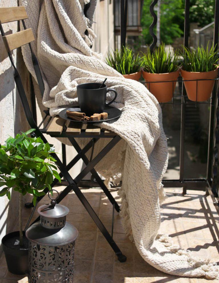 Stuhl auf Balkon mit Deko und Kafeetasse