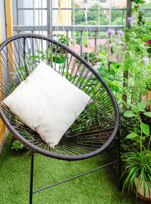 Balkon mit Stuhl und Kissen auf Kunstrasen und Pflanzen