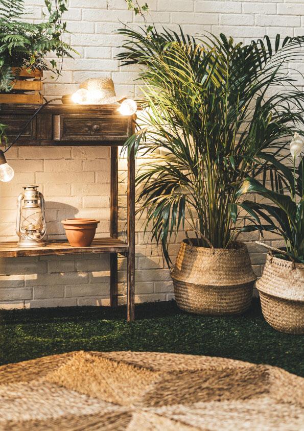 Sisal-Teppich und die Bambus-Körbe mit Pflanzen und Kunstrasen auf Balkon