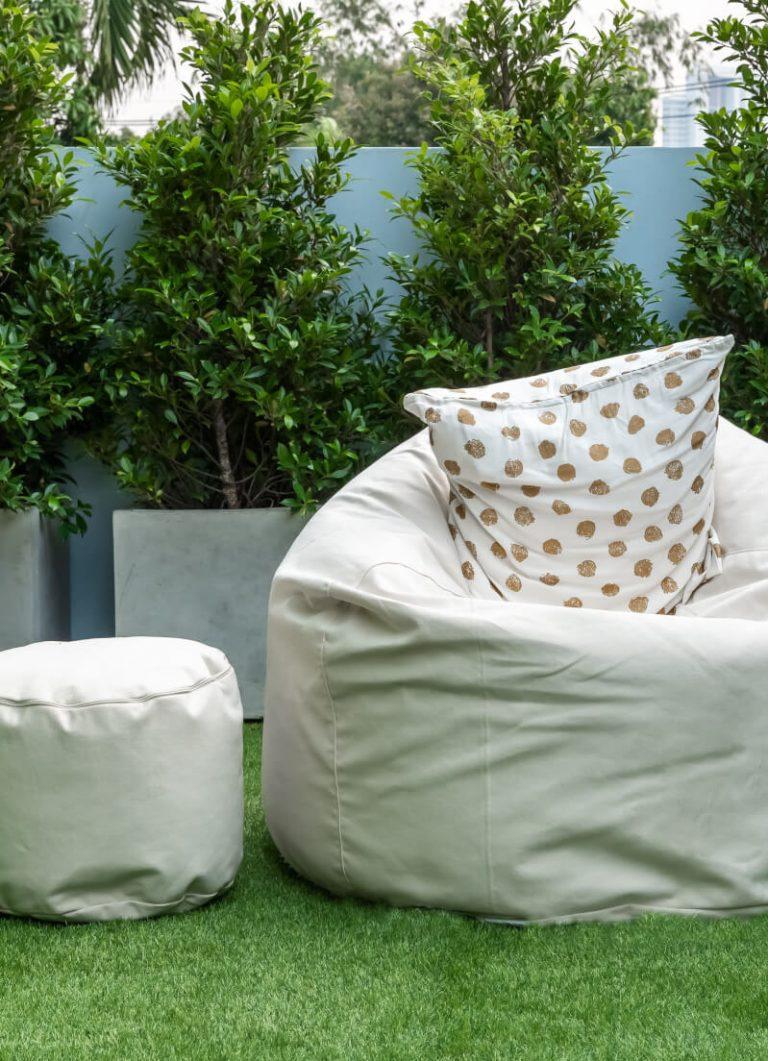 Sitzsack und Hocker auf Balkon mit Pflanzen iim Hintergrund