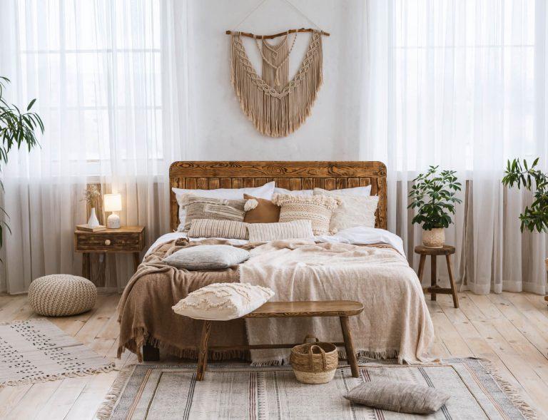 Schlafzimmer mit Natur-Holzbett, Makramee-Wandbehang, hellen Gardinen und heller und brauner Bettwäsche