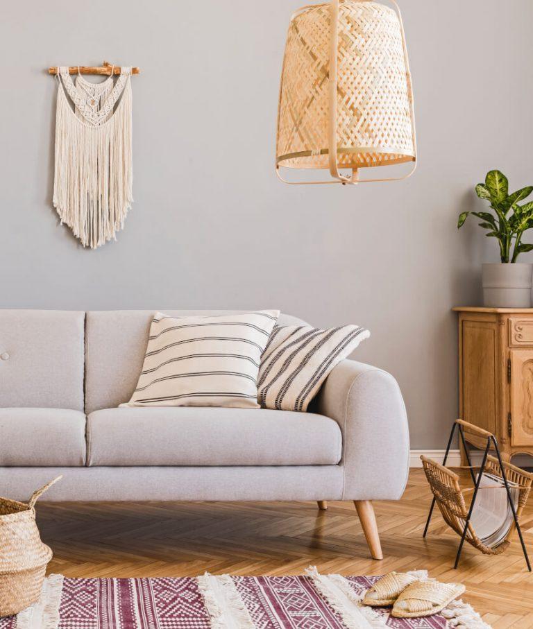 Helles Sofa, Makramee Wandbehang, Lampe aus Rattan und Musterteppich mit Fransen