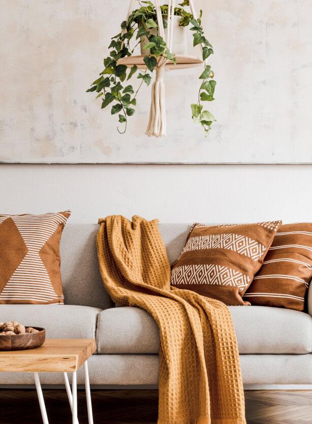 Helles Sofa mit Kissen und Decke in Erdfarben