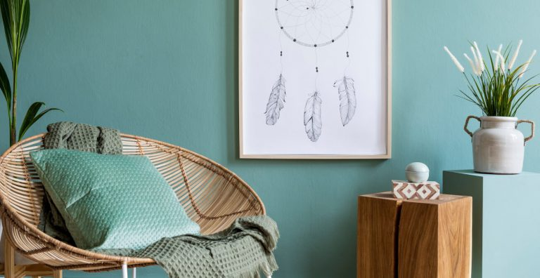 Raum gestrichen in gedecktem Türkiston mit Korbsessel, Kissen und Traumfängerbild an der Wand