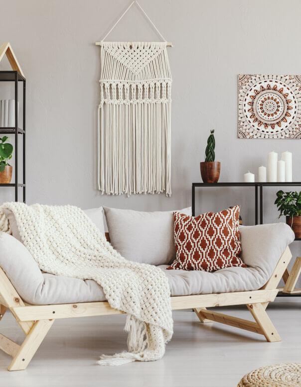 Wandbehang aus Makramee und helles Sofa