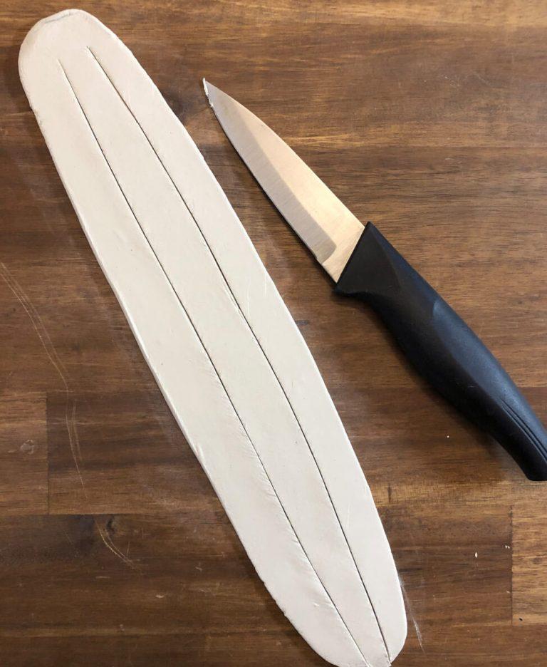 Modelliermasse ausgerollt, eingeschnitten mit Messer daneben