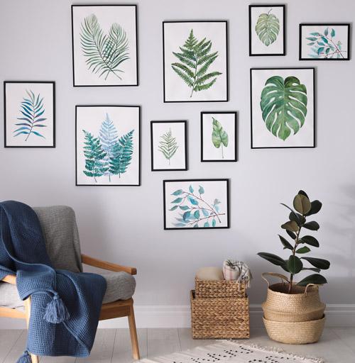 Bilderrahmen mit Blättermotiven an hellgrauer Wand, davor Sessel mit dunkelblauer Decke