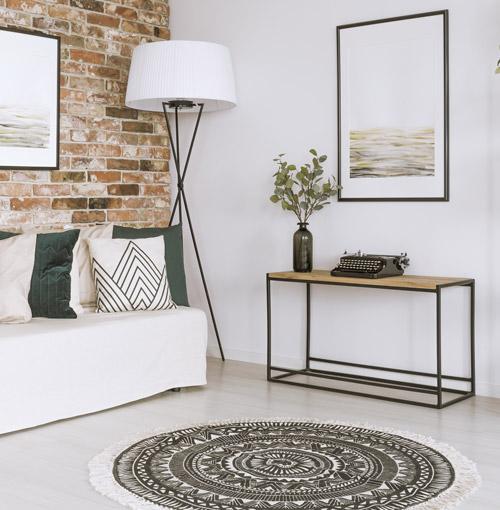 Sofa mit Kissen vor Wand in Backsteinoptik davor runder Teppich mit Franzen