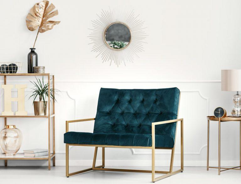 Sessel in Samt mit Metall in gold vor heller Wand