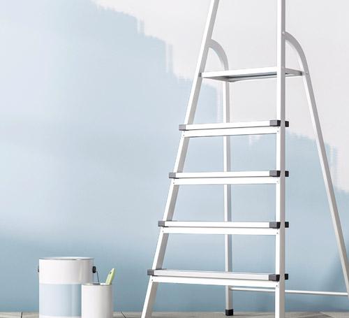 Metallleiter und Farbeimer vor hellblau gestrichener Wand