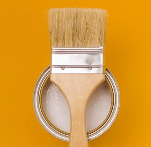 Pinsel liegt auf Farbdose mit orangenem Hintergrund