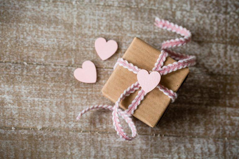 Kleines Geschenk mit rosafarbenen Band Herzen
