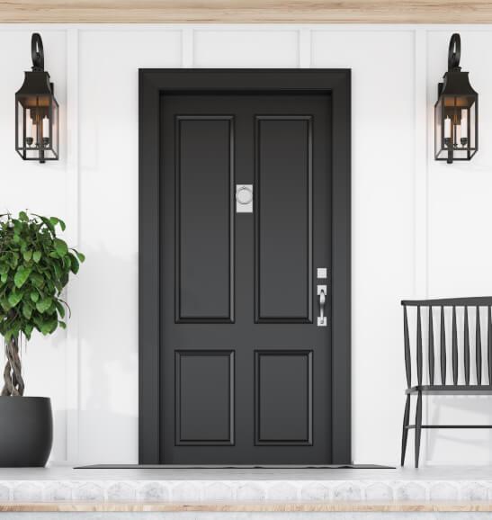 Eingang mit schwarzer Tür, Laternen, Stuhl und Pflanze