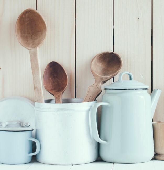 Emaille-Kannen und -Becher mit Holzkochlöffeln