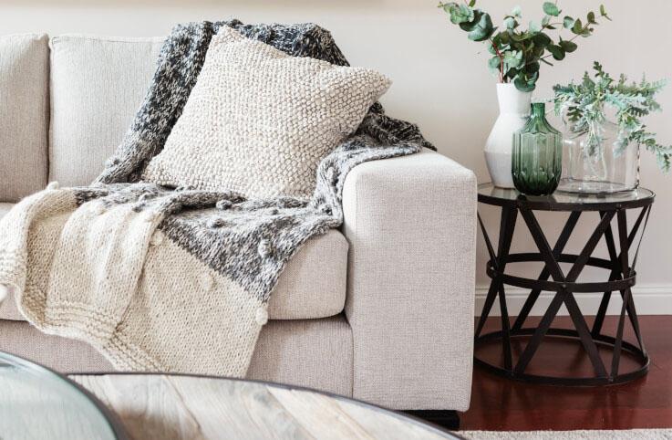 Sofa mit grob gestrickter Decke und Kissen