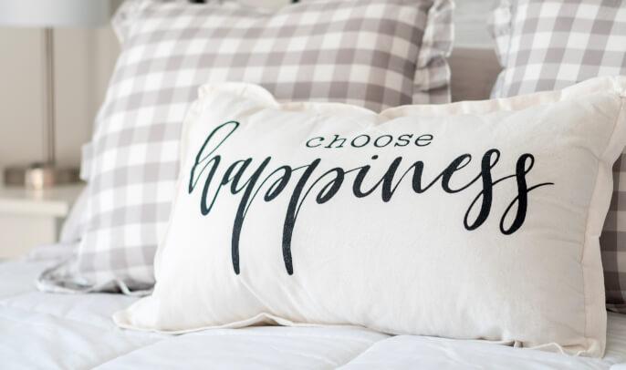 Kariertes Kissen und weißes Kissen mit Spruch choose happiness
