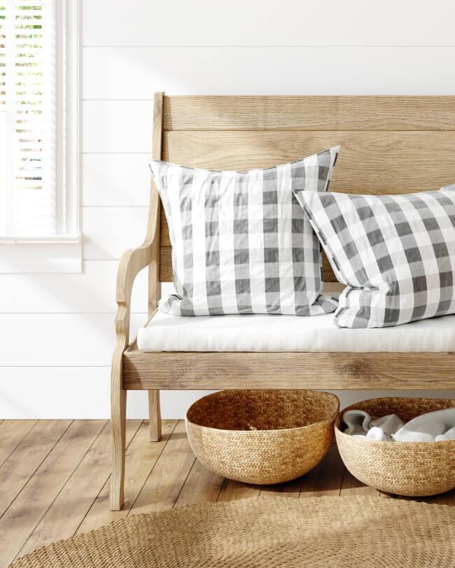 Naturbelassene Holzbank mit karierten Kissen