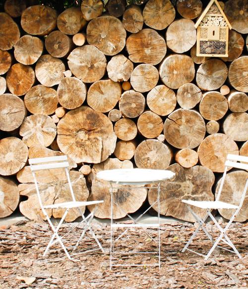 gesapelte Holzstämme mit Tischgruppe davor