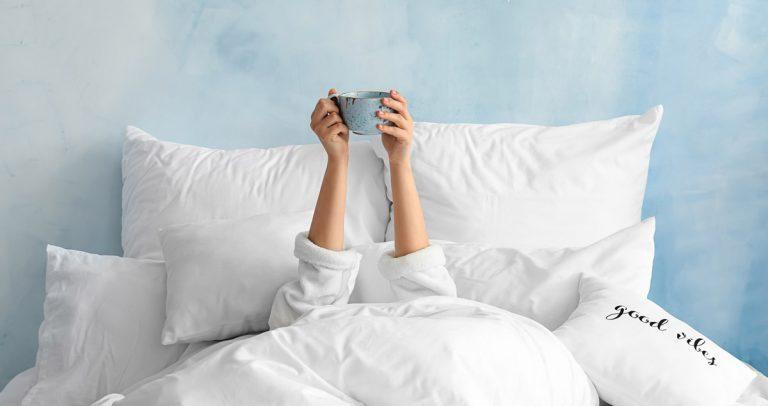 Frau liegend im Bett und hält eine Tasse hoch